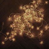 Christmas lights garland on old vintage wooden parquet floor, to Royalty Free Stock Photos