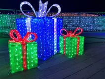 Christmas lights gift box, illuminated presents at night. Christmas gift box made from lights in blue and red color with red and white ribbon. Three huge big royalty free stock images