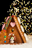 Christmas lights and gingerbread house. Gingerbread house against a background of christmas tree lights royalty free stock photo