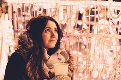 Christmas lights and girl holding coffee Royalty Free Stock Images
