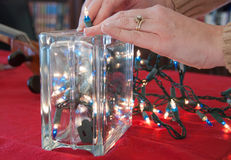 Christmas Lights in a Glass Block. A Christmas decoration is being made out of a glass block and a string of Christmas lights Stock Photos