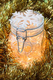 Christmas Lights in a Glass Jar. And a Golden Garland Stock Photos