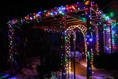 Christmas lighting up the Winter Snow. Christmas lights glowing around the Pergola and small Arbor showing off the merriness of the season Stock Photos