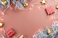 Christmas lights, golden ornaments, red giftbox and fir branches on brown background Stock Photos