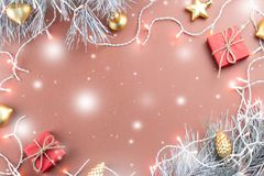 Christmas lights, golden ornaments, red giftbox and fir branches on brown background, copy space Stock Images
