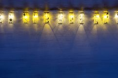 Christmas lights lanterns burn on blue ultramarine wooden background. New Year festive home interior Royalty Free Stock Photos