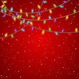Christmas Lights. Multicolored garland christmas lights on red, silk background with falling snow Stock Images