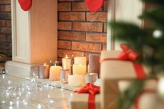 Christmas lights near decorative fireplace with candles. Indoors royalty free stock image