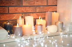 Christmas lights near decorative fireplace indoors. Christmas lights near decorative fireplace with candles indoors royalty free stock images
