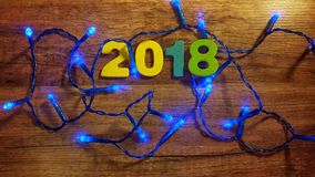 Christmas lights and number 2018  on wooden background Royalty Free Stock Photography