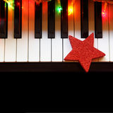Christmas lights and ornament on piano Stock Photography