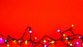 Christmas lights over red background. Colorful border with empty copy space for text royalty free stock images