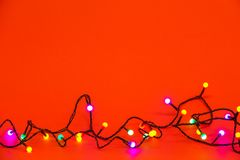 Christmas lights over red background. Colorful border. With empty copy space for text royalty free stock image