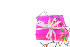 Christmas lights and packaged gift on white background Stock Photo