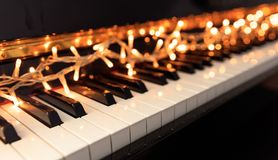 Christmas lights on a piano keyboard. Christmas lights on a classical piano keyboard royalty free stock photography