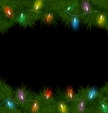 Christmas lights on pine on black Royalty Free Stock Images