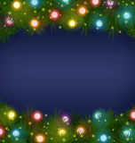 Christmas lights on pine on blue Royalty Free Stock Photos