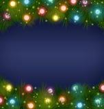 Christmas lights on pine on blue Royalty Free Stock Photos