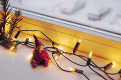 Christmas lights, pine branch and cute elf. Window with Christmas lights, pine branch and cute elf royalty free stock images