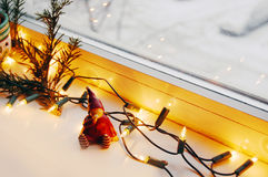 Christmas lights, pine branch and cute elf. Window with Christmas lights, pine branch and cute elf stock photos