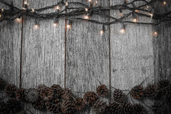 Christmas Lights and Pine cones on Rustic Wood Stock Image