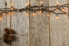 Christmas Lights and Pine cones on Rustic Wood Stock Photography