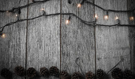 Christmas Lights and Pine cones on Rustic Wood Royalty Free Stock Photos