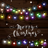 Christmas lights poster with shining and glowing garlands. On wooden background Lettering Merry Christmas. Web banner vector illustration Royalty Free Stock Photo