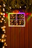 Christmas lights reflected in old window of rustic red painted w stock photography