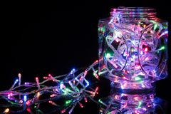 Christmas lights on reflective black background. Holiday shiny garland border. Xmas lights concept stock photography