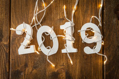 2019 with christmas lights. On rustic wooden background Stock Images