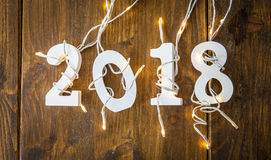 2018 with christmas lights. On rustic wooden background Royalty Free Stock Image