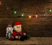 Christmas lights with snow man and santa claus doll on wood bac royalty free stock photo