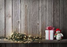 Christmas lights, snowman toy and gift box Stock Photography