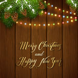 Christmas lights and snowy pine branches on brown wooden backgro. Holiday lettering Merry Christmas and Happy New Year on brown wooden background with winter Royalty Free Stock Photography