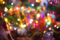 Christmas Lights Star Bokeh. Festive background with star shaped bokeh from Christmas tree lights glowing Royalty Free Stock Images
