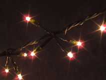 Christmas Lights Strand. Single strand of lit Christmas lights against a dark background. Lights have a starlight filtered glow royalty free stock photo