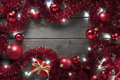 Christmas Lights Tinsel Background. A background of Christmas presents, red tinsel, ornaments and fairy lights on a rustic wood background Stock Photo