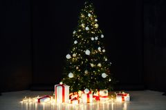 Christmas lights with Christmas tree and gifts on a black background