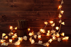 Christmas lights on a vintage brown wooden background. New Year background stock image