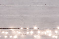 Christmas lights on white painted wooden background with copy sp Royalty Free Stock Photos