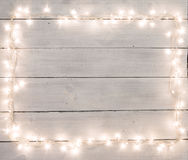 Christmas lights on white painted wooden background with copy sp Stock Image