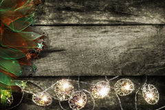 Christmas lights on wood. A bare wood surface with white Christmas lights across the bottom of the frame.  Colorful cloth with stars on one border Royalty Free Stock Photography