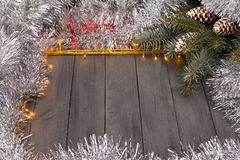 Christmas lights on a wooden background with free space. Frame with silver christmas chain. Royalty Free Stock Images
