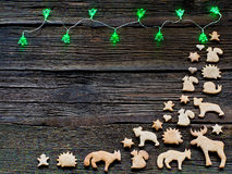 Christmas lights on a wooden background with free space. Gingerbread in the shape of animals, stars and hearts Royalty Free Stock Photography