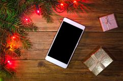 Christmas lights on a wooden background and smartphone, top view Stock Photography