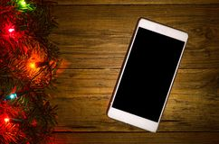 Christmas lights on a wooden background and smartphone, top view Royalty Free Stock Photo