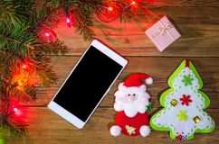 Christmas lights on a wooden background and smartphone, top view Stock Photo