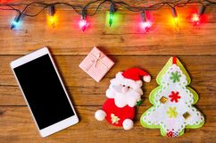 Christmas lights on a wooden background and smartphone, top view Stock Photos