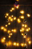 Christmas lights on wooden board. Shaped like Christmas tree  with some baubles Royalty Free Stock Photo
